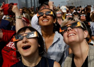 People watch the solar eclipse from the observation deck of The Empire State Building in New York