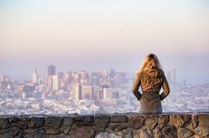 Woman sits on wall looking out over a city